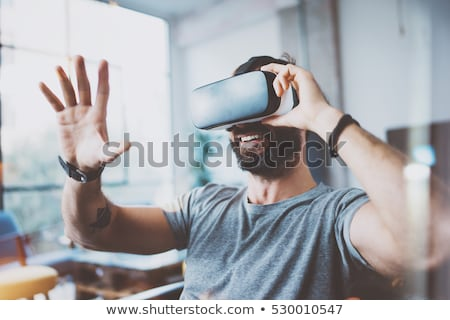 young man in virtual reality headset or 3d glasses stock photo © dolgachov