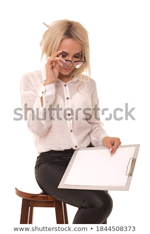A beautiful young girl sits in a chair in the office and holds a notebook in her hand. Stock photo © Traimak