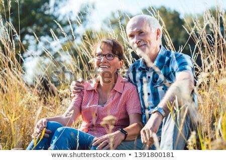senior couple sitting in the grass enjoying themselves stock photo © kzenon