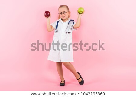 Foto d'archivio: Little Girl In Doctor Costume With Apples