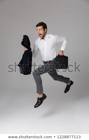 full length image of successful businessman 30s walking and hold stock photo © deandrobot