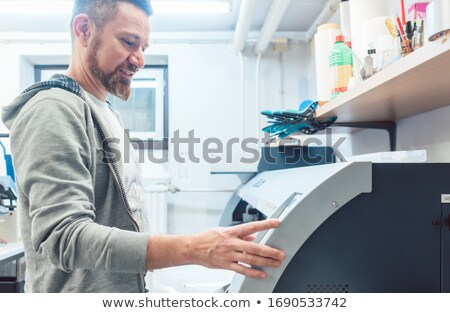 Man working on large format printer in advertising agency Stock photo © Kzenon