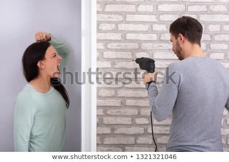 Neighbor Man Using Power Drill On Brick Wall Stock photo © AndreyPopov