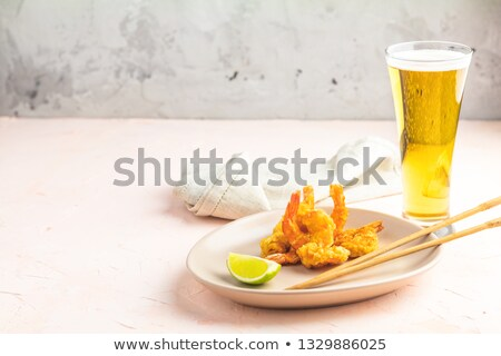 Shrimps tempura and glass of beer on pink concrete surface Stock photo © artsvitlyna