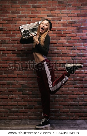 Full length image of stylish hip hop woman 20s, standing against Stock photo © deandrobot