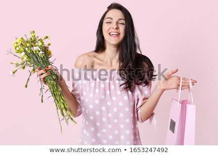 Stylish gorgeous brunette in red with red roses and red bag. Stock photo © studiolucky