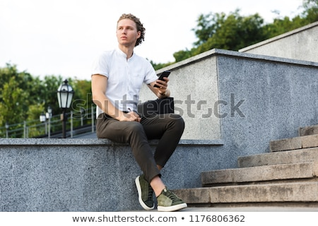 Photo stock: Serious Curly Business Man With Briefcase Holding Smartphone
