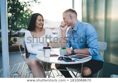 Loving couple sitting in cafe outdoors while talking with each other. stock photo © deandrobot