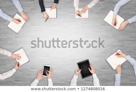 Group of people with devices in hands having desk discussion and working on laptops, tablets in team Stock photo © ra2studio