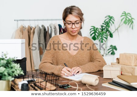 Young female customer in eyeglasses and pullover checking list of ordered goods Stock photo © pressmaster