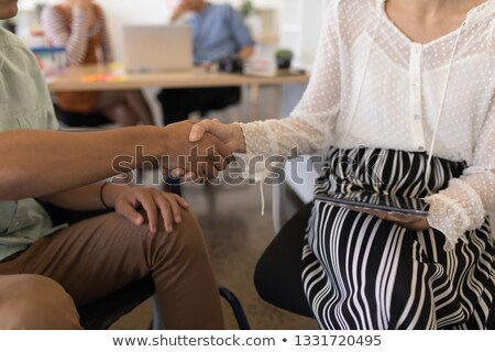 Mid section of disabled male executive shaking hands with his casually dressed coworker in office Stock photo © wavebreak_media