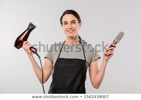 Happy young brunette hairdresser in apron holding hairdryer and hairbrush Stock photo © pressmaster