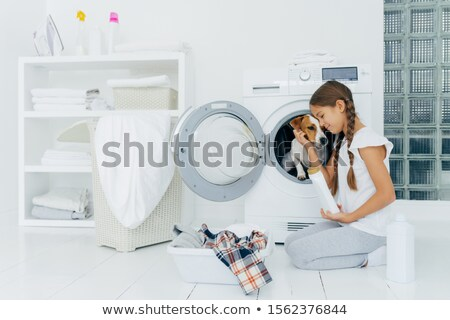 Small child plays with dog russell terrier, poses on knees near washing machine, busy with housekeep Stock photo © vkstudio