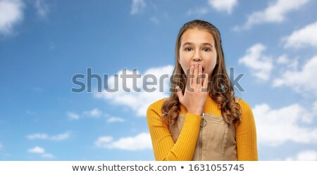 shocked teenage girl covering her mouth over sky Stock photo © dolgachov