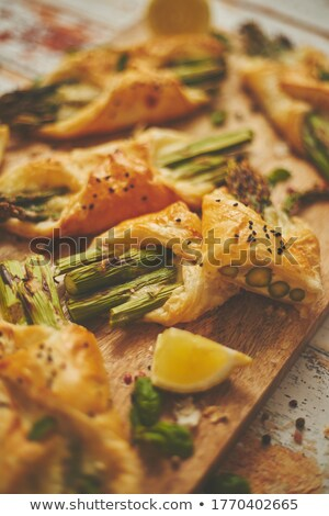 Baked green asparagus wrapped in puff pastry. Served on wooden board. With selective focus Stock photo © dash