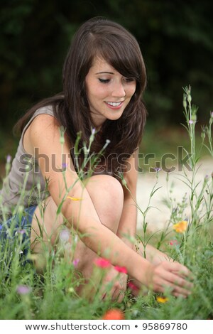 Сток-фото: Young Woman Picking Wildflowers From The Side Of A Pathway