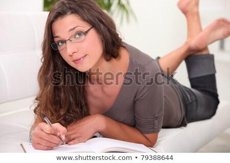 Fiatal nő szemüveg mezítláb kanapé ír könyv Stock fotó © photography33