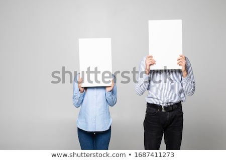 casual people hiding their faces behind a blank banner stock photo © feedough