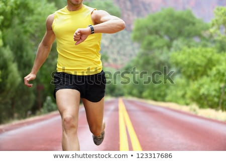 Male runner looking at his heart rate monitor. Stock photo © luckyraccoon