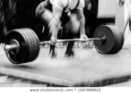 Man workout with barbell on the bench Stock photo © deandrobot