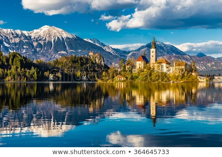 catholic church in bled lake and bled castle slovenia at sunris stock photo © kayco