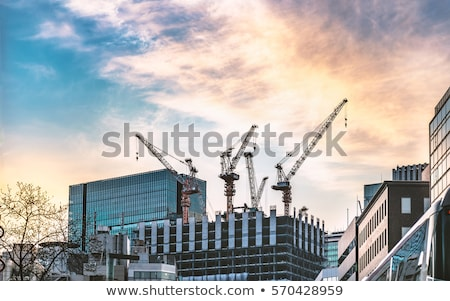Buildings under construction and cranes under a blue sky Stock photo © zurijeta