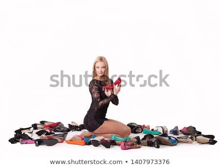 Attractive blonde lady next to many pairs of high heel shoes Stock photo © konradbak