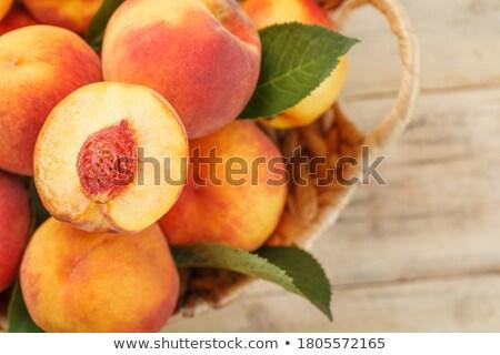 Fresh juicy peaches with leaves on dark wooden rustic background Stock photo © yelenayemchuk