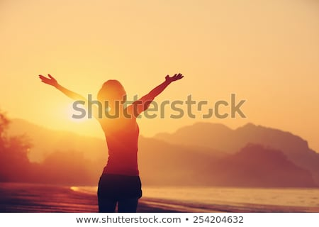 Happy woman with arms outstretched standing at beach Stock photo © wavebreak_media