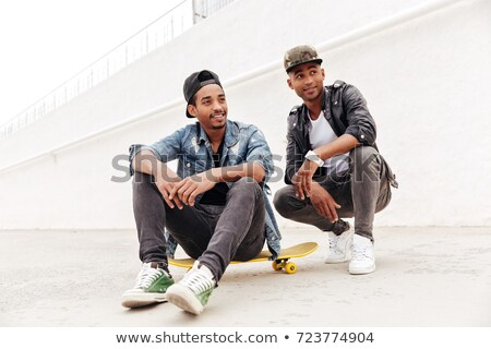 African men friends walking outdoors sitting with skateboard Stock photo © deandrobot