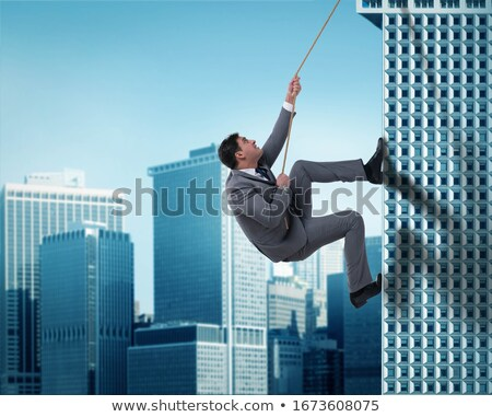 Businessman climb a skyscraper. Achievement business goal and difficult career concept Stock photo © alphaspirit