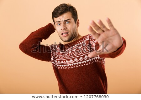 Image of displeased man 20s with stubble wearing knitted sweater Stock photo © deandrobot