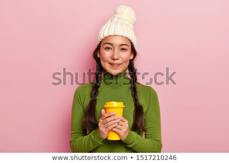 Image of two pleased women wearing hats holding takeaway coffee, Stock photo © deandrobot