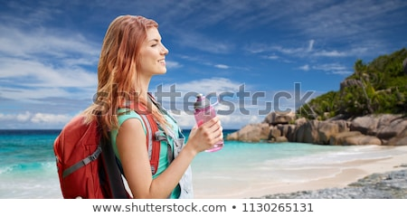 happy woman with backpack over seychelles beach stock photo © dolgachov