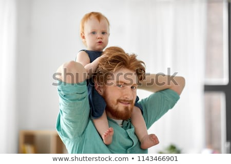 father carrying his little baby daughter on neck stock photo © dolgachov