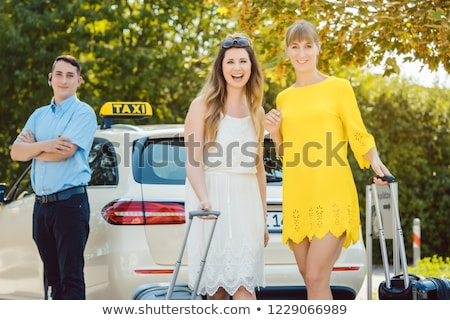 best friends getting out of taxi from shopping trip in town stock photo © kzenon