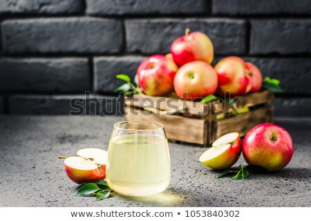 glass of homemade organic apple cider with fresh apples in box on wooden background space for text stock photo © denismart