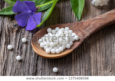 Homeopathic pills on a spoon and Vinca minor plant Stock photo © madeleine_steinbach
