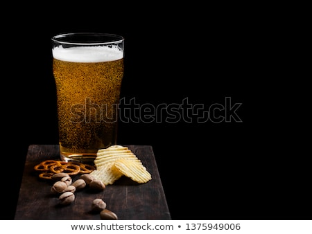 Glass of lager beer with snack on stone board on black background. Pistachios and pretzel with potat Stock photo © DenisMArt