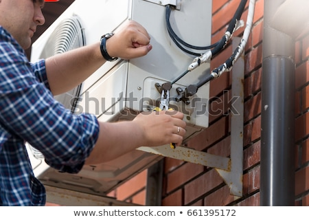 Male Technician Repairing Air Conditioner Outdoors Stock photo © AndreyPopov