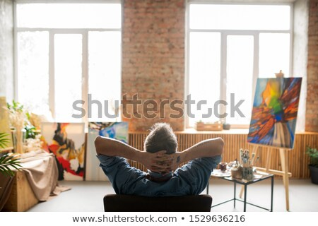 Rear view of restful professional painter sitting in armchair in studio Stock photo © pressmaster