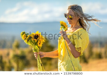 Happy woman holding sunflowers hair blowing in the wind Stock photo © lovleah
