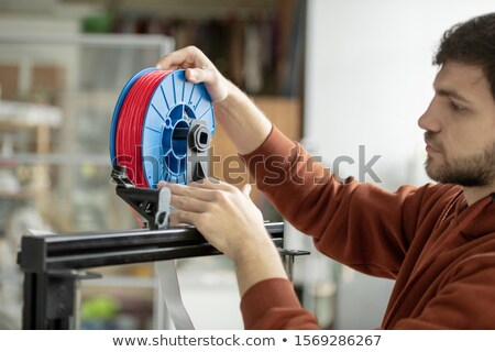 Young designer putting spool with red filament in 3d printer to print new items Stock photo © pressmaster