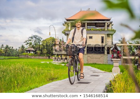 A young man rides a bicycle on a rice field in Ubud, Bali. Bali Travel Concept Stock photo © galitskaya