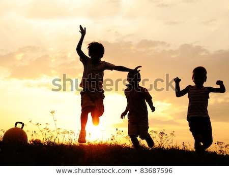 Foto d'archivio: Silhouette Group Of Happy Children Playing On Meadow Sunset Summertime
