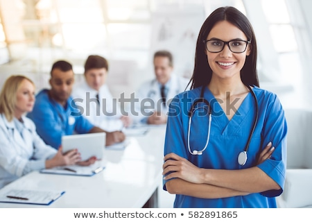 Smiling female nurse looking at notes Stock photo © photography33