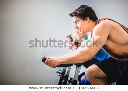 Young man on stationary training bicycle Stock photo © elly_l