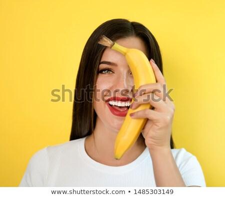 beautiful brunette holds a banana stock photo © cboswell