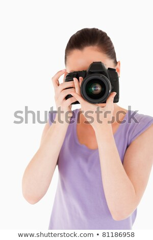 Charming woman using a camera while standing against a white background stock photo © wavebreak_media