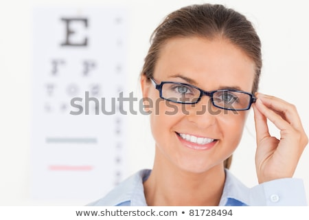 Portrait of a brunette eye specialist wearing glasses looking into the camera in her surgery Stock photo © wavebreak_media